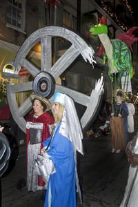 Saint Catherine pulling a giant wheel, with Saint Margaret behind with her dragon