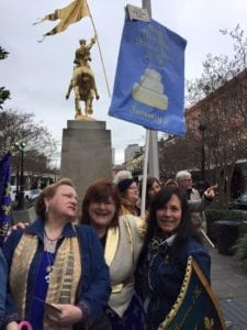 Krewe members waving Joan's birthday banner at the statue at the 2016 second line.